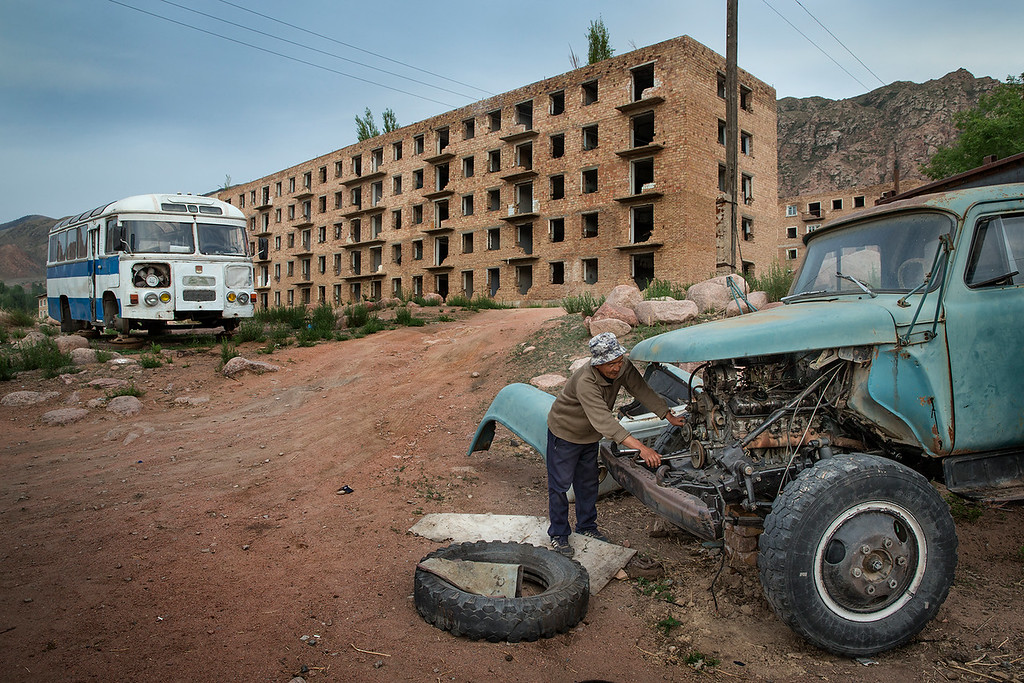Local man working on an old car in front of broken down buildings in Kadji-Sai. The buildings were built by German prisoner of war during WWII, when Kyrgyzstan was part of the Soviet Union.
