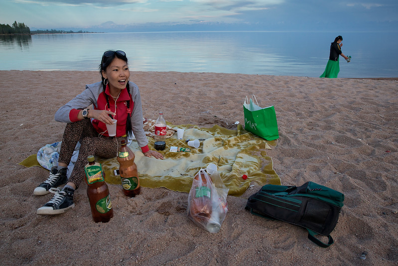 Woman drinking beer and having a picnic on the shores of Issyk-Kul Lake.