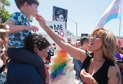 Grand Marshal Michaela Mendelsohn feeds the first bite of wedding cake to her young son while on her wife's shoulders