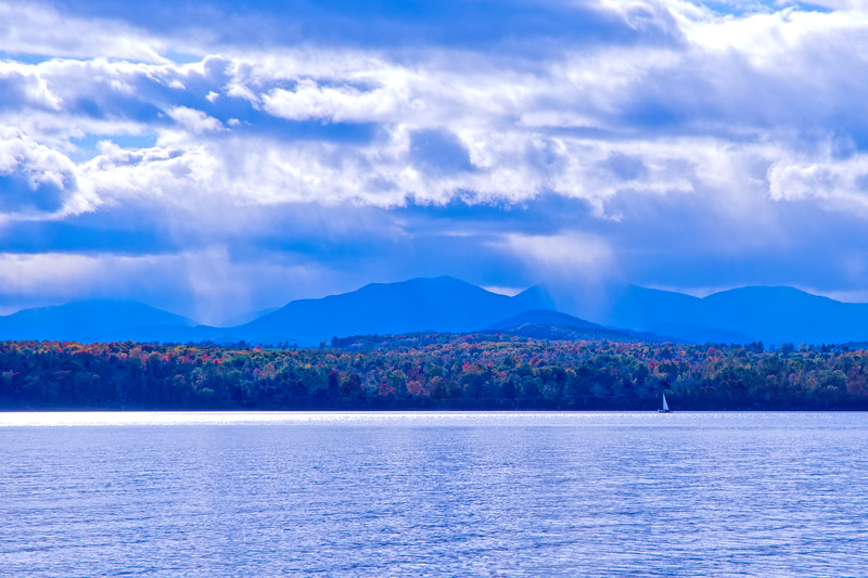 Shoreline with Adirondack mountain range, peak foliage, puffy clouds & sun rays • Lake Champlain, NY • 2014