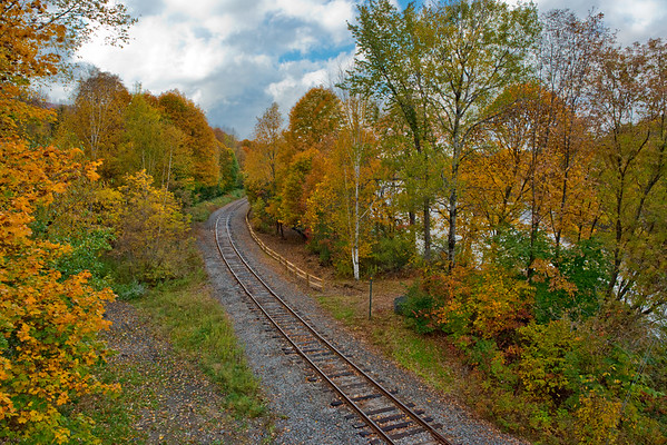 Train tracks in peak fall foliage along river • Wells, Adirondack Park, NY • 2015