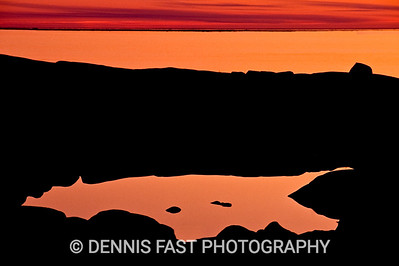 """SUNSET REFLECTION OVER HUDSON BAY.  Northern landscapes are among my personal favorites. This photo was made over a very small pool hidden among the rocks overlooking Hudson Bay in Churchill, Manitoba, Canada. By choosing a wide-angle lens and picking just the right point of view, I was able to create an interesting shape in the dark foreground that also mirrored the quiet sunset. I love the resulting """"reflective"""" mood!"""