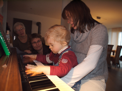 Monday 17th Dec 2007 - maybe Cai is the next Mozart!<br /> <br /> We visited kerstin's sister for her birthday, Cai loves playing the piano, even without his hearing aids, we are not sure what the neighbours think, but Sabina said that they all know abou Cai and if she tells them it was him making the noise all will be fine.<br /> <br /> I  was in the UK to visit my eldest son Michael and rest of my family and friends, we didnt have the same drama like last time, however we were woken early this morning by the night nurse (kinder spitex) , when kerstin didn't  come back to bed I guessed it was more than we had run out of something and went to see what was going on. I found a lot of activity centered around Cai, he had wheezy breath and was having difficulty breathing, a bit like an asthma attack, so we gave him some medicine. He spent most of the day looking very sorry for himself, sleeping or sitting on someones knee. At just after 6 pm I lay him flat on my knee to reach something and he turned blue then gray and made a huge cough, I started to consider how to reach the ambi bottle and call for help when I saw a huge amount of gunk coming out of his unblocked nostril and mouth, a quick suction and wipe over with the magic sponge and he was off pushing his trolley five minutes later. He still sounds wheezy but not as bad as before. <br /> <br /> we wonder if it was the fire you see in the background of the above picture that caused his reaction