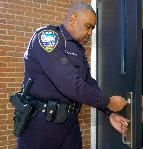 CLAY-SFUL 12.14.11 ANCHOR 4<br />  Fulton County Resource Officer Arthur Armstrong checks entrance doors outside Mcnair Middle School.<br /> PHOTO BY JOE LIVINGSTON/STAFF