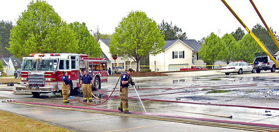 Douglas Firefighters from Station 11 from left, Tara Anderson, Todd Arbeau and Jeremy Toney clean equipment after extinguishing a blaze that destroyed most of the Autum Village strip mall located at the corner of Hwy. 92 and Brickleberry Way in Douglasville.