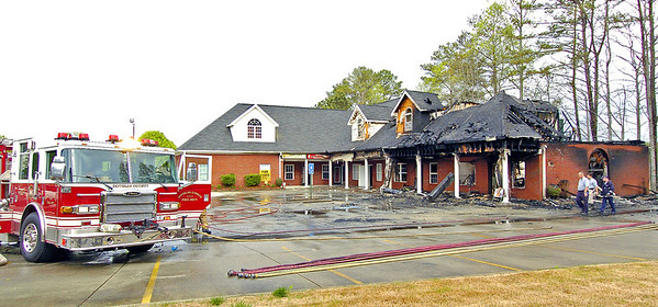 Douglas County Fire Officials look over whats left of a blaze that destroyed most of the Autum Village strip mall located at the corner of Hwy. 92 and Brickleberry Way in Douglasville.