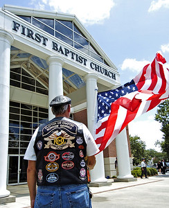 Patriot Guard Rider Alan Bergman from Monticello holds a flag at the entrance to the funeral of slain Clayton County Police Officer Rick Daly.