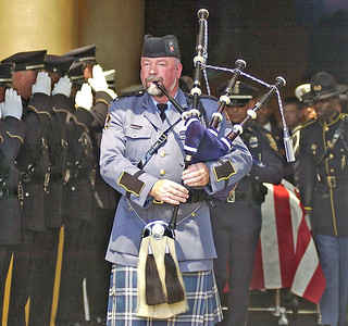 Bagpipe player Dan Bray from the Georgia State Patrol plays Amazing Grace as the casketof slain Clayton County Police Officer Rick Daly is escorted out.