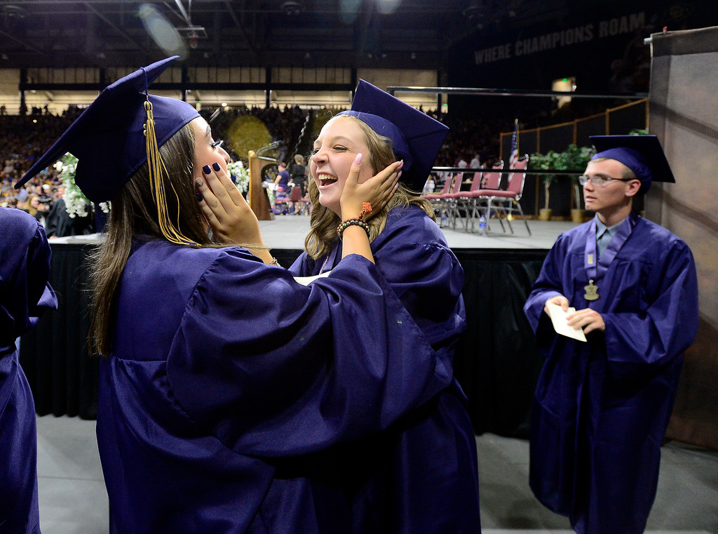 . Paige Stevens, right, the senior class speaker,  rushes off the stage to greet fellow graduate Jessica Whitcomb at the Legacy High School Graduation at the Coors Events Center on the CU Boulder Campus Wednesday evening. For more photos go to dailycamera.com Paul Aiken Staff Photographer May 16, 2018