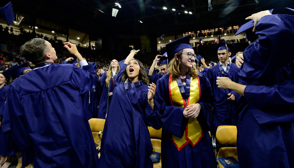 . Alexis Macha tosses her cap into the air as fellow grad Liliana Maisano watches her classmates hug at the end of the Legacy High School Graduation at the Coors Events Center on the CU Boulder Campus Wednesday evening. For more photos go to dailycamera.com Paul Aiken Staff Photographer May 16, 2018