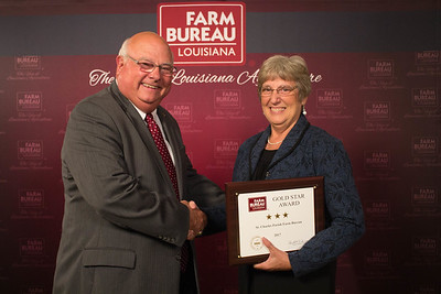 St. Charles Farm Bureau Parish President Joan Robbins accepts the Three Gold Star Award from Louisiana Farm Bureau President Ronnie Anderson.