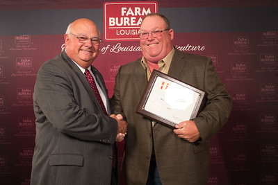 Bossier Farm Bureau Parish President Loyd Dodson accepts the Three Gold Star Award from Louisiana Farm Bureau President Ronnie Anderson.
