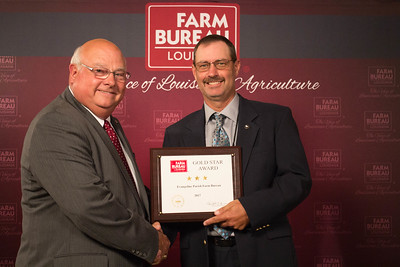 Evangeline Farm Bureau Parish President Scott Fontenot accepts the Three Gold Star Award from Louisiana Farm Bureau President Ronnie Anderson.