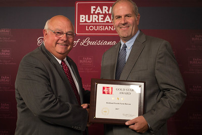 Richland Farm Bureau Parish President Hunter Fife accepts the Three Gold Star Award from Louisiana Farm Bureau President Ronnie Anderson.