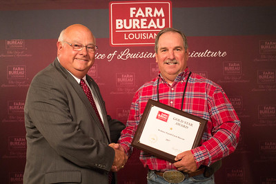 Webster Farm Bureau Parish President Joe Lynn Robinson accepts the One Gold Star Award from Louisiana Farm Bureau President Ronnie Anderson.
