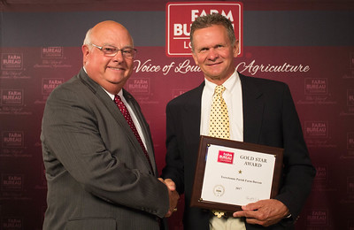 Terrebonne Farm Bureau Parish President Tom Ellender accepts the One Gold Star Award from Louisiana Farm Bureau President Ronnie Anderson.