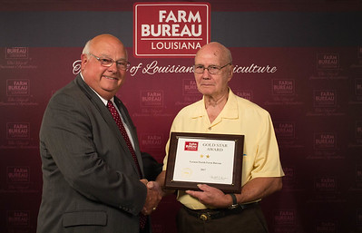 Vernon Farm Bureau Parish President G.A. Holaway accepts the Two Gold Star Award from Louisiana Farm Bureau President Ronnie Anderson.
