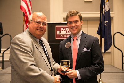 Wesley Adolph of Assumption Parish receives his award for participating in the 2018 Talk Meet from Louisiana Farm Bureau President Ronnie Anderson.