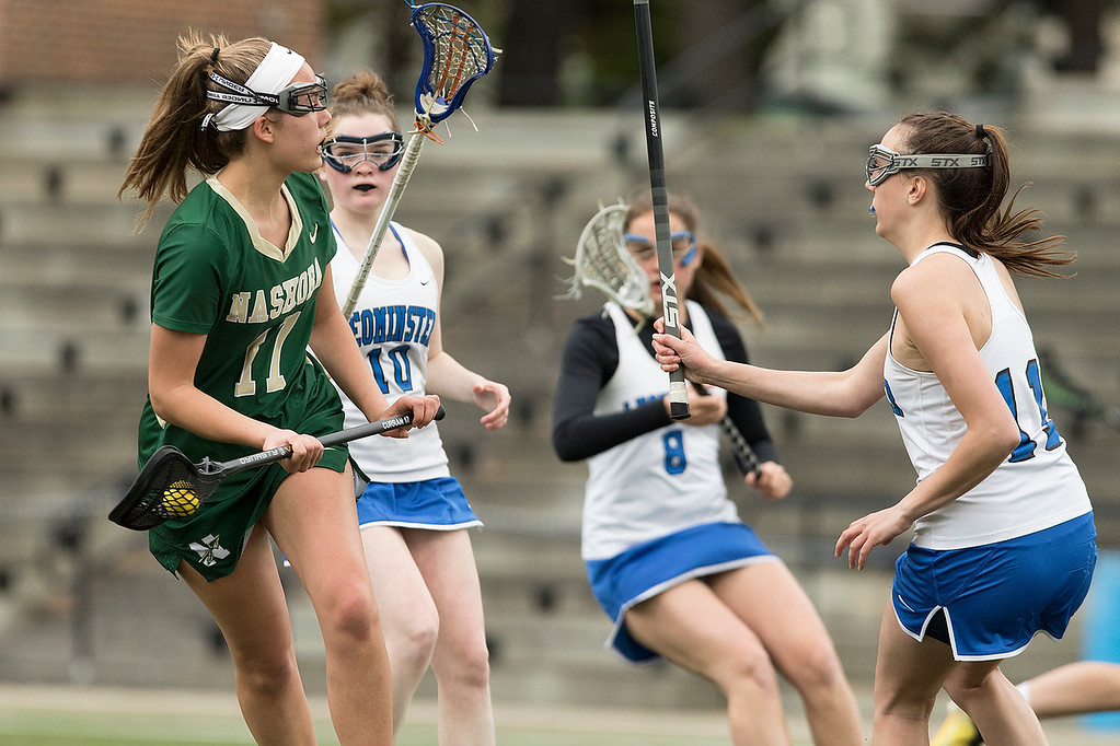 . Nashoba Regional High School girls lacrosse played Leominster High School at Doyle Field in Leominster on Tuesday, April 30, 2019. LHS\'s Eliza Howlett plays some defense as NRHS\'s Shhauna Curran looks to pass the ball to an open teammate. SENTINEL & ENTERPRISE/JOHN LOVE