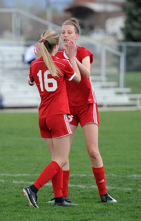 . Ava Hannaford (16) and Livia McQuade celebrate after McQuade\'s goal against Frederick on Friday, April 26 at Mountain View Field. Loveland won 5-0. (Colin Barnard/Loveland Reporter-Herald)