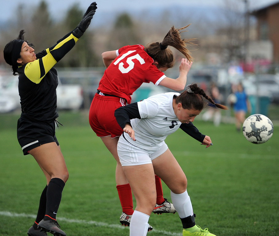 . Carissa Morrison takes on Frederick\'s defense on a header attempt on Friday, April 26 at Mountain View Field. Loveland won 5-0. (Colin Barnard/Loveland Reporter-Herald)