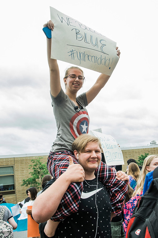 . Daniel Livingston and Erica Frazier hold signs as students at Leominster High School walk out of class on Friday, June 16, 2017 to protest the nearly 100 school district faculty and staff that are facing layoffs because of a $5.6 million school district budget deficit. The protest moved as far as City Hall where they were greeted by Mayor Dean Mazzarella. SENTINEL & ENTERPRISE / Ashley Green