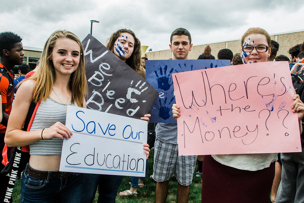 . Mariah Kaczov, Kylee Heap, Tyler Nacke and Ariana Garvia hold signs as students at Leominster High School walk out of class on Friday, June 16, 2017 to protest the nearly 100 school district faculty and staff that are facing layoffs because of a $5.6 million school district budget deficit. The protest moved as far as City Hall where they were greeted by Mayor Dean Mazzarella. SENTINEL & ENTERPRISE / Ashley Green