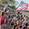 Nashoba Regional High School football played Leominster High School on Saturday afternoon, Sept. 28, 2019  in Bolton during the Ken Tucker Memorial Game. NRHS students wave an American flag as senior Isabelle Sonia, with microphone, sang the national anthem to start the game off. SENTINEL & ENTERPRISE/JOHN LOVE