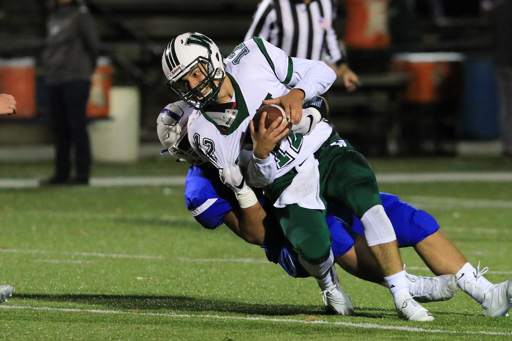 . Wachusett senior Melke is pulled down by Leominster senior captain Zachary Khallady in Friday night\'s football match up between Wachusett and Leominster at Doyle Field.  SENTINEL & ENTERPRISE/JOHN LOVE