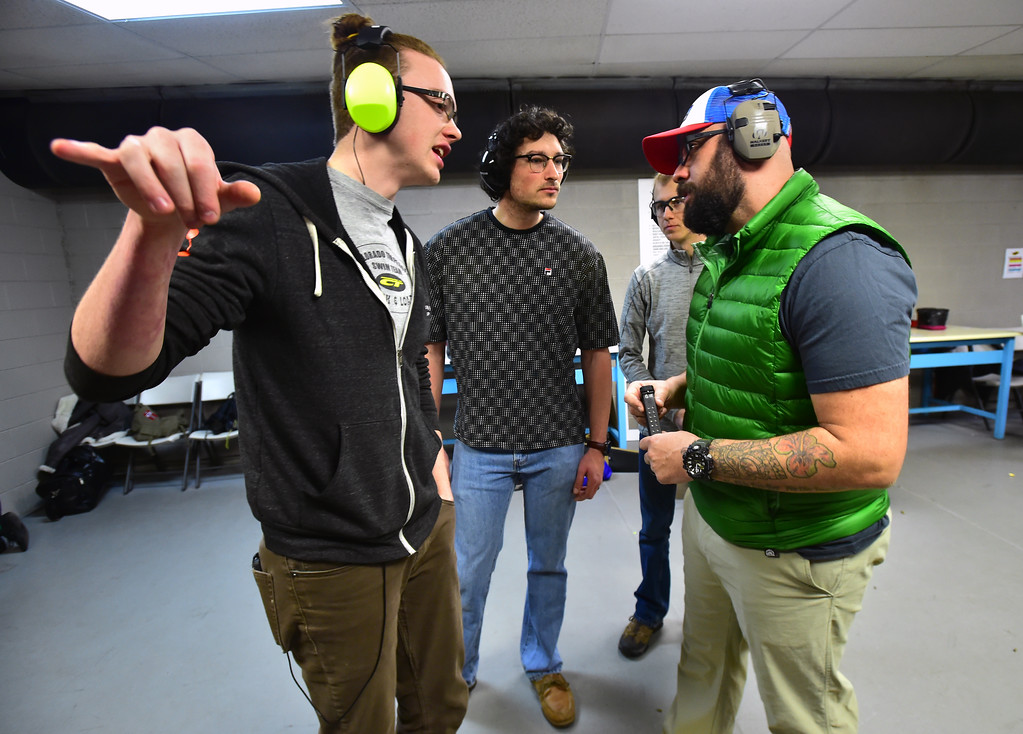. From left to right Benjamin Farmer, Evan Gutzait, Trevor Mohlenkamp and Fernando Rebora of the Flatirons Sights shooting group chat during their shooting session at the Shoot Indoors range in Broomfield on Sunday February 4, 2018.  For more photos and a video go to dailycamera.com Paul Aiken / Staff Photographer / Feb 4, 2018