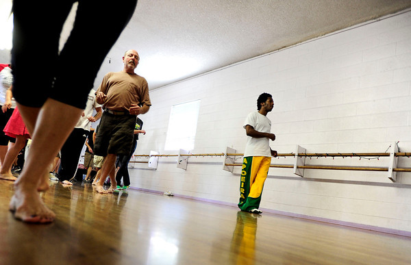 "From left, Luciana da Silva, of Colorado Springs moves her feet for a beginners solo samba class in Kakes studio to watch as Phil Loff, of Longmont and Bryan Saunders, of Denver dance. The samba class is a part of the Colorado Brazil Festival, highlighting different types of dance. August 4, 2012. Rachel Woolf/ For the Daily Camera. For more photos and a video of the class, go to  <a href=""http://www.dailycamera.com"">http://www.dailycamera.com</a>."
