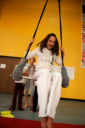 Students from the Legacy Academy Charter school's 8th grade Physical Science class watch Jessicca Wolf, 14, spin on a trapeze as they learn the physics behind her spin at the Frequent Flyers' aerial dance studio in Boulder, Colorado January 26, 2010.  FOR THE CAMERA/Stephen Swofford