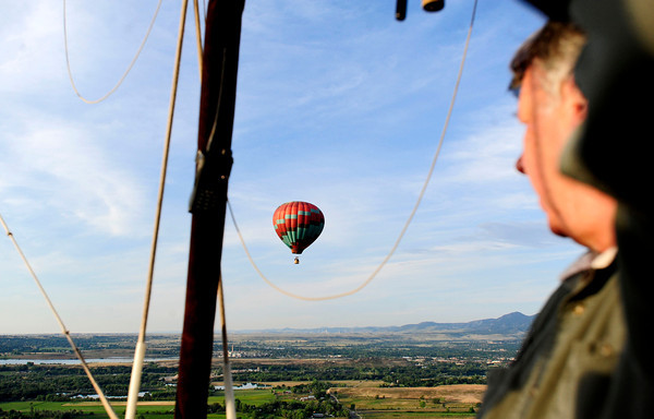 Sunny Day Come Fly Away's Pilot Tommy Cederlund, of Broomfield looks to another balloon during flight Sunday morning in Boulder, Colorado. July 15, 2012. Rachel Woolf/ For the Daily Camera