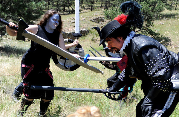 """F0931LARP11.jpg Lore Master David McMillen, right, playing Athos the Musketeer, is hit by morb Jen Allgood while her and other morbs attack McMillen and the rest of his Live Action Role Playing team during a LARPing event at Heil Ranch North of Boulder on Saturday, Aug 1, 2009.   Watch the video at  <a href=""""http://www.dailycamera.com"""">http://www.dailycamera.com</a>.<br /> <br /> Photo by Mara Auster/Daily Camera"""