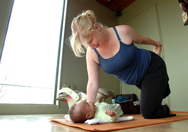 "Amanda Nuku with her son Dzinuvi Nuku 8 weeks old, holds a pose during the  Mommy and Me class at Yo Mama Yoga on Tuesday May 28, 2010. Amanda Nuku with her son Dzinuvi Nuku 8 weeks old. For a video and more photos of the class go to  <a href=""http://www.dailycamera.com"">http://www.dailycamera.com</a>. <br /> Photo by Paul Aiken /"