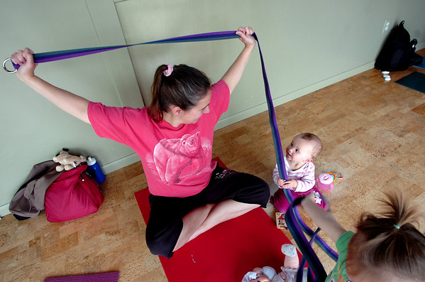 """Carrie Hill holds a yoga pose while Lia Houle, 10 months, looks on Mommy and Me class at Yo Mama Yoga on Tuesday May 28, 2010. For a video and more photos of the class go to  <a href=""""http://www.dailycamera.com"""">http://www.dailycamera.com</a>. Lia Houle's mom Katie was participating in the class.<br /> Photo by Paul Aiken /"""