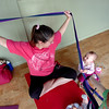 "Carrie Hill holds a yoga pose while Lia Houle, 10 months, looks on Mommy and Me class at Yo Mama Yoga on Tuesday May 28, 2010. For a video and more photos of the class go to  <a href=""http://www.dailycamera.com"">http://www.dailycamera.com</a>. Lia Houle's mom Katie was participating in the class.<br /> Photo by Paul Aiken /"