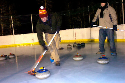 Doug Jones and Matt Flynn sweep in front of a rock during play of the Nederland Curling Club at the NedRINK - Nederland Ice & Racquet Park on Monday February 15, 2010. Photo by Paul Aiken / The Camera Watch a video and see more photos of the Nederland Curling Club at www.dailycamera.com