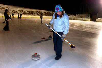 Nancy Stubbs prepares to sweep in front of a rock during play of the Nederland Curling Club at the NedRINK - Nederland Ice & Racquet Park on Monday February 15, 2010. Photo by Paul Aiken / The Camera Watch a video fo the Nederland Curling Club at www.dailycamera.com