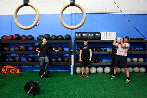 "20120206_CROSSFIT_BANDEL.jpg Boulder resident Gary Pawlas lifts a concrete ball while Shawn Bandel, center, and Bill Prestor watch and support him at CrossFit in Louisville, Colo. on Monday, Feb. 6, 2012. Bandel, one of the gym's owners, says they seek to make people feel confident mentally with what they are doing physically. ""It's an environment of encouragement,"" says Bandel. (Morgan Varon)"