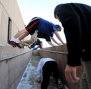George Grell, top left, joins other members of the fairview Parkour Club move down the walls of a walk way outside the school. For more photos of the Parkour, go to www.dailycamera.com. Cliff Grassmick/ January 29, 2010
