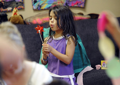 Cali Hernandez blows a pin wheel during her psychic class. Psychic courses for children focus on giving children the tools to learn to stay connected to their inner knowing, understand their personal space and help them connect to what is true and important for them. For more photos, go to www.dailycamera.com. Cliff Grassmick / July 21, 2012