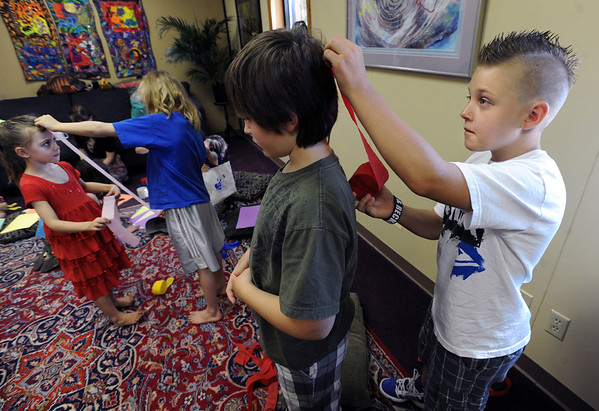 "Matthew Smith, right, measures the line that will be used for chakras on his brother, Ethan. Lina McCombs, left, is getting measured by her sister, Julian.<br /> Psychic courses for children focus on giving children the tools to learn to stay connected to their inner knowing, understand their personal space and help them connect to what is true and important for them.<br /> For more photos, go to  <a href=""http://www.dailycamera.com"">http://www.dailycamera.com</a>.<br /> Cliff Grassmick / July 21, 2012"