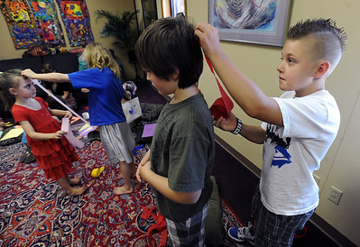 Matthew Smith, right, measures the line that will be used for chakras on his brother, Ethan. Lina McCombs, left, is getting measured by her sister, Julian. Psychic courses for children focus on giving children the tools to learn to stay connected to their inner knowing, understand their personal space and help them connect to what is true and important for them. For more photos, go to www.dailycamera.com. Cliff Grassmick / July 21, 2012