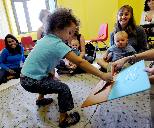 "Arabella Snyder, 3, puts a dinosaur on the board after getting instructions in French from teacher, Veronique Carney at the WOW Children's Museum in Lafayette. Amy Giaquinto and her son, Gabriel, 15-months, are watching on the right.<br /> For more photos and a video of the language class, go to  <a href=""http://www.dailycamera.com"">http://www.dailycamera.com</a><br /> Cliff Grassmick / April 25, 2012"