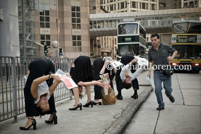 Yoga teachers Julie Choi (L), Margaretha Burenstam Linder, Samantha Russel and Alexander Medin, all living in Hong Kong. Perform a yoga pose (tittibhasana) while reading a newspaper on Des Voeux Rd, in Central Hong Kong.