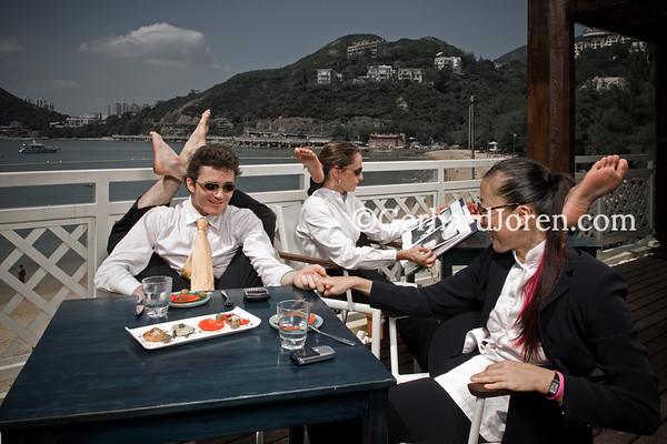 Yoga teachers Julie Choi (R), Samantha Russel and Alexander Medin( CL), all living in Hong Kong. Alexander's pose is dvi-pada sirsasana, Julie and Samntha's pose, eka-pada sirsasana, while chatting restaurant Cococabana in Deep Water Bay,  Hong Kong.