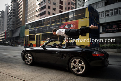 Alexander Medin, a Norwegian yoga teacher living in Hong Kong. Perform a yoga pose (mayurasana) on a moving car, in Wan Chai, Hong Kong.