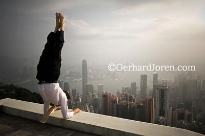 Alexander Medin, a Norwegian yoga teacher living in Hong Kong. Perform a yoga pose (pincha mayurasana) on the roof of a building at The Peak, overlooking Central Hong Kong.