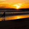 Surfer walking in sunset